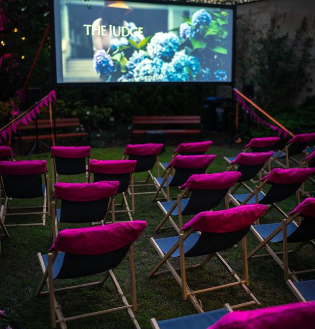 Zdjęcie przedstawia pokaz kina plenerowego w ogrodzie - grupa ludzi na leżakach przed ekranem, na którym jest wyświetlany film. Fot. Ł. Gryko